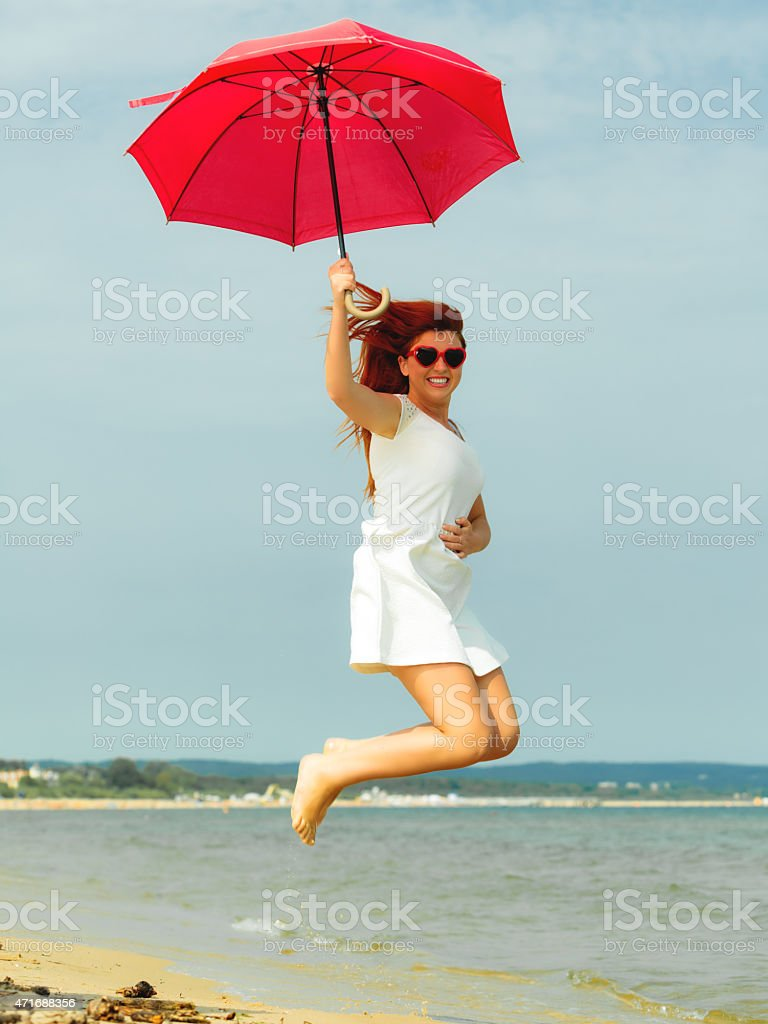 Redhaired girl jumping with umbrella on beach stock photo
