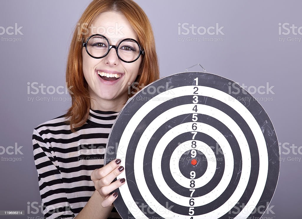 Red-haired girl with dartboard. royalty-free stock photo