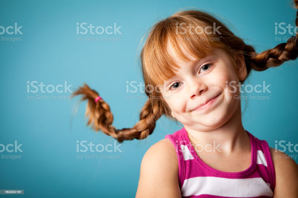 Red-Haired Girl with Upward Braids, a Smile and Dimples stock photo