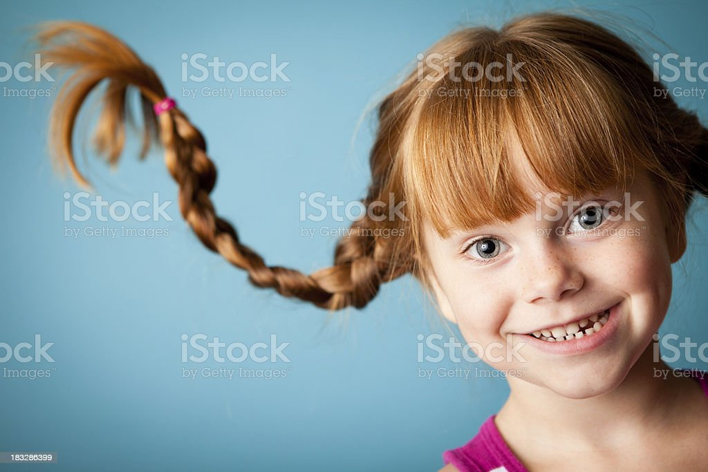 Red-Haired Girl with Upward Braids and a Big Smile stock photo