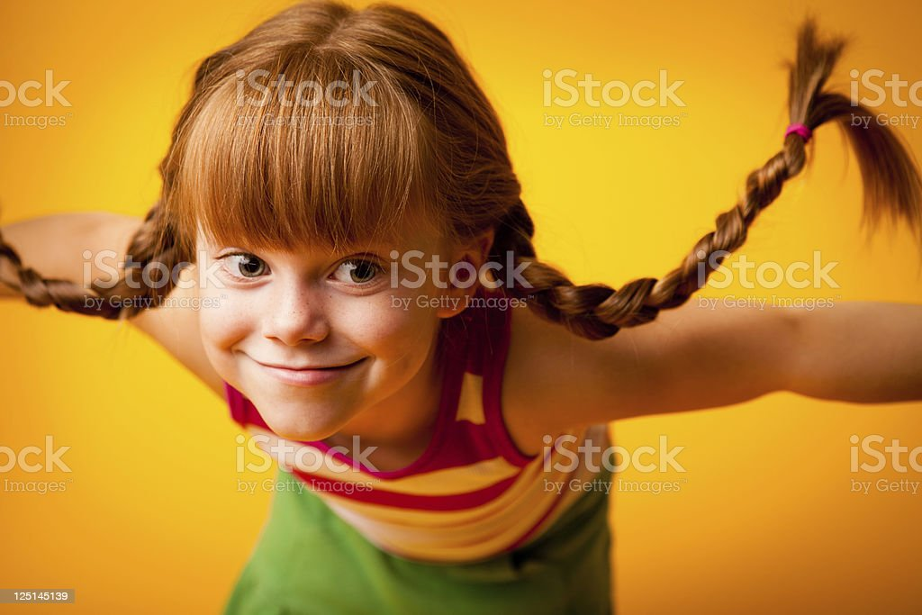 Red-Haired Girl with Upward Braids and Goofy Grin stock photo