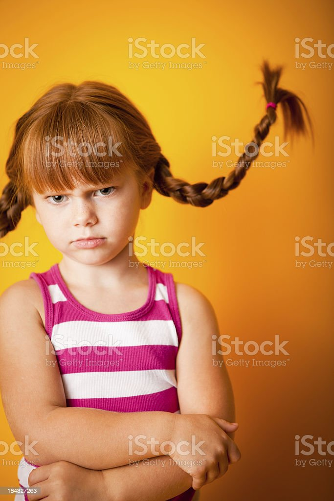 Red-Haired Girl with Upward Braids and Grumpy Face stock photo