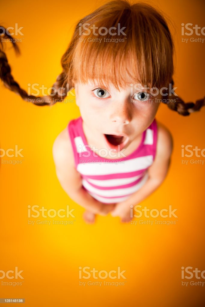 Red-Haired Girl with Upward Braids and Look of Surprise royalty-free stock photo