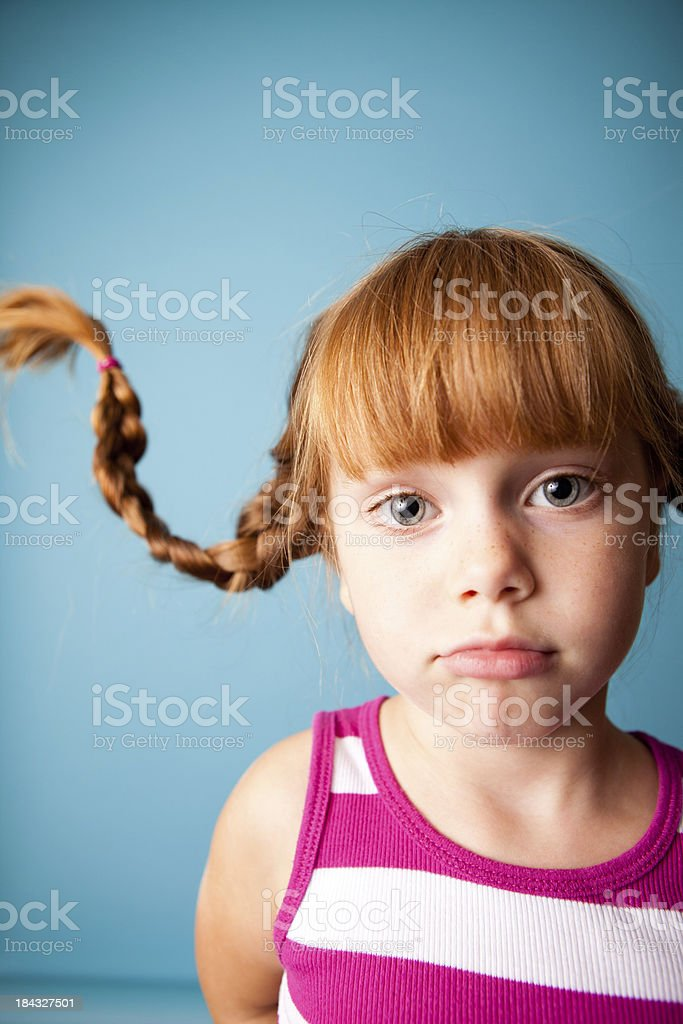 Red-Haired Girl with Upward Braids and Strange Look stock photo