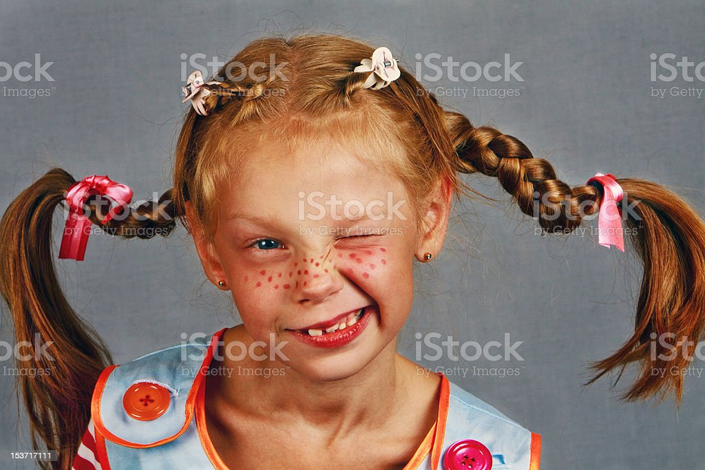 Red-Haired Girl with Upward Braids are winks Making  Face stock photo