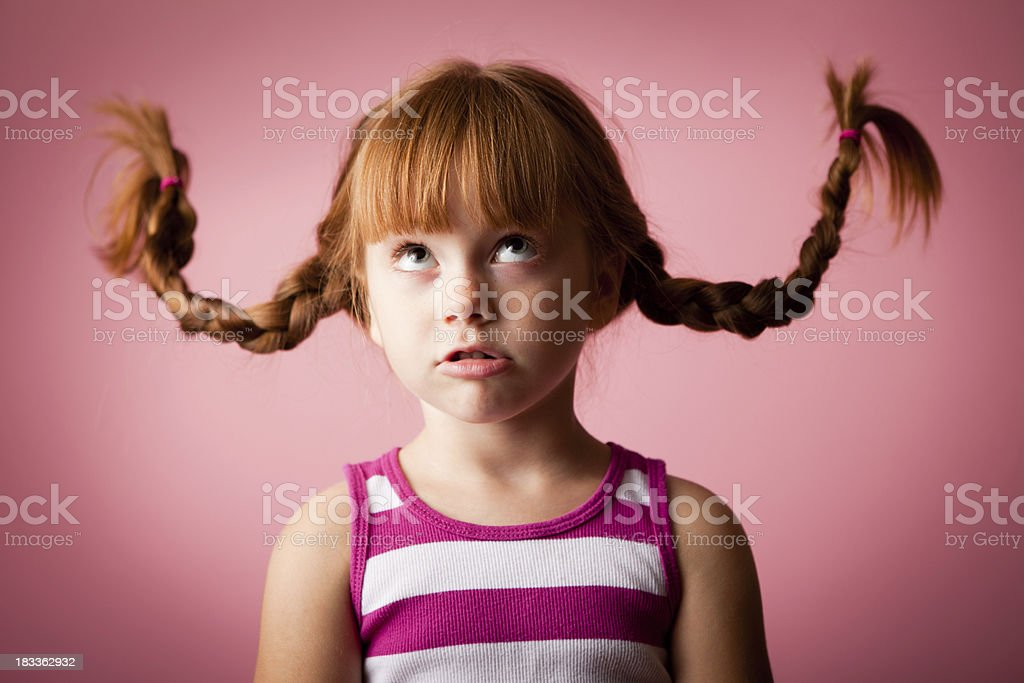 Red-Haired Girl with Upward Braids on Pink Background royalty-free stock photo