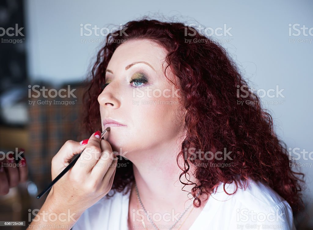 Red-haired lovely girl in a hairdressing salon makes  professional stock photo