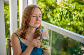Red-haired woman drinking a mojito on the terrace