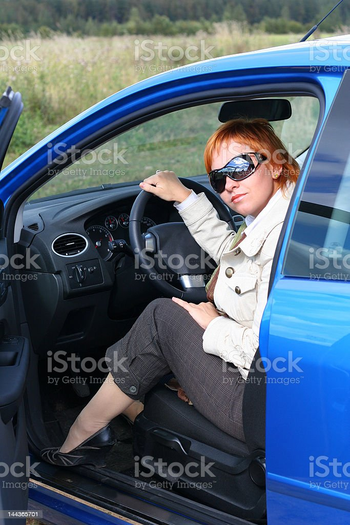 Red-haired woman in sun glasses with blue car royalty-free stock photo