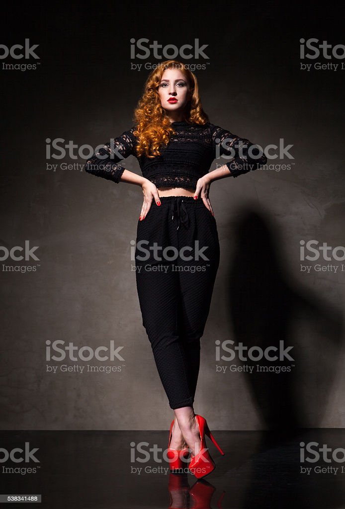 Red-haired woman posing against of black wall in light stock photo