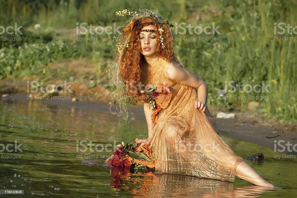 Red-haired woman sitting in water. stock photo