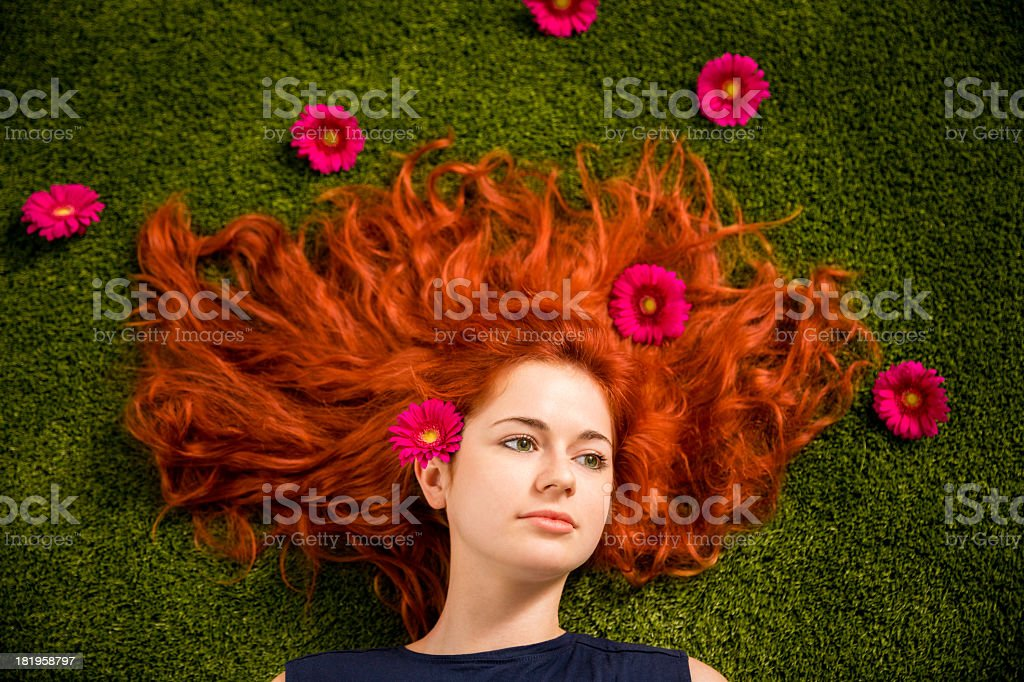 Redhaired woman with blossoms lying on grass in park royalty-free stock photo