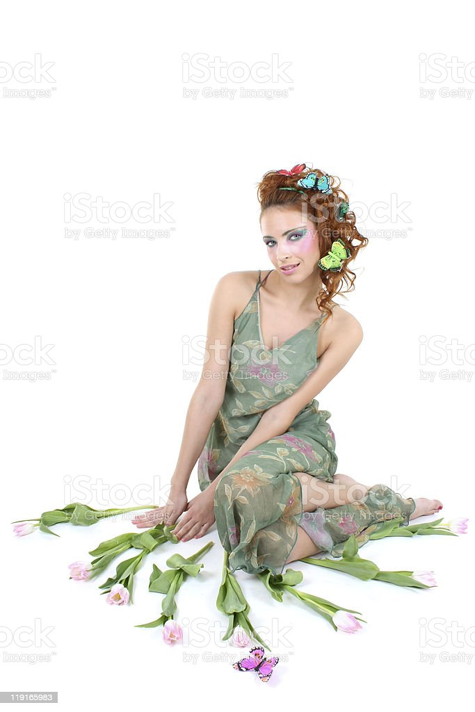 Red-haired woman with flowers and butterflies sitting stock photo