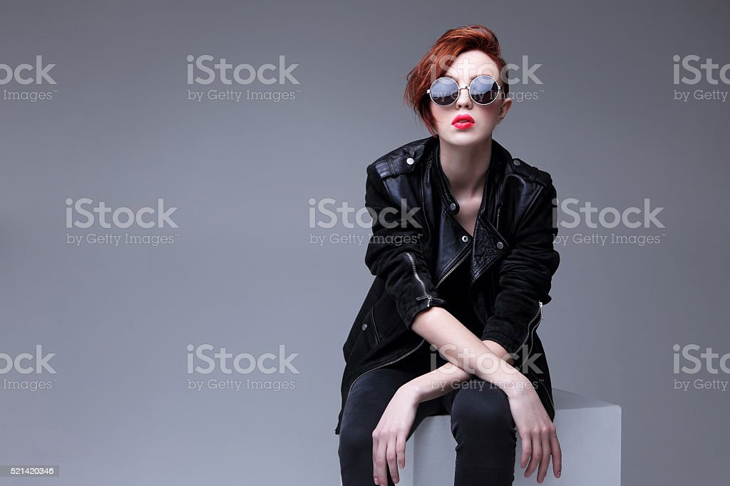 Redhead fashion model in sunglasses and black leather jacket stock photo