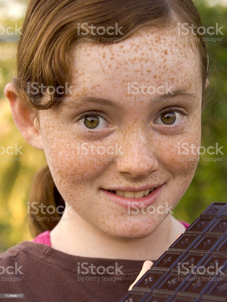 Redhead Freckle Face Girl with Big Eyes, Chocolate Bar Temptation royalty-free stock photo