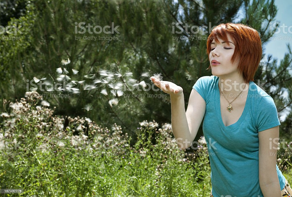 Redhead Girl Blowing Fuzzy Flower Seeds In Spring Air, Breeze royalty-free stock photo