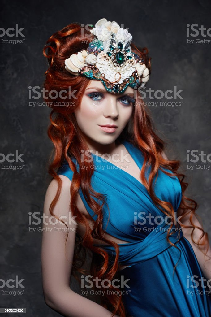 Redhead girl fabulous look, blue long dress, bright makeup and big eyelashes. Mysterious fairy woman with red hair. Big eyes and colored shadows, long lashes. Sexy look, Princess on a dark background stock photo