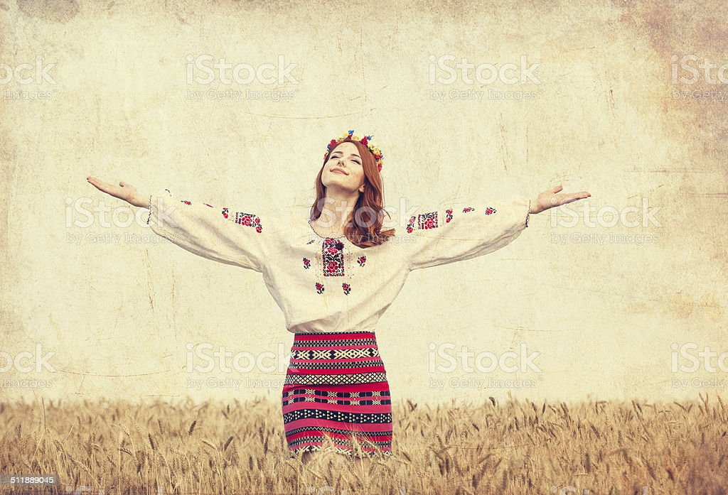 Redhead girl in national ukrainian clothes on the wheat field. stock photo