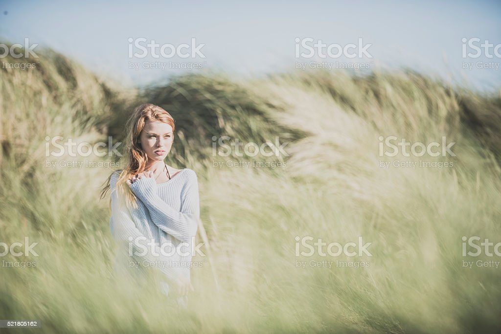 Redhead girl in the dunes stock photo
