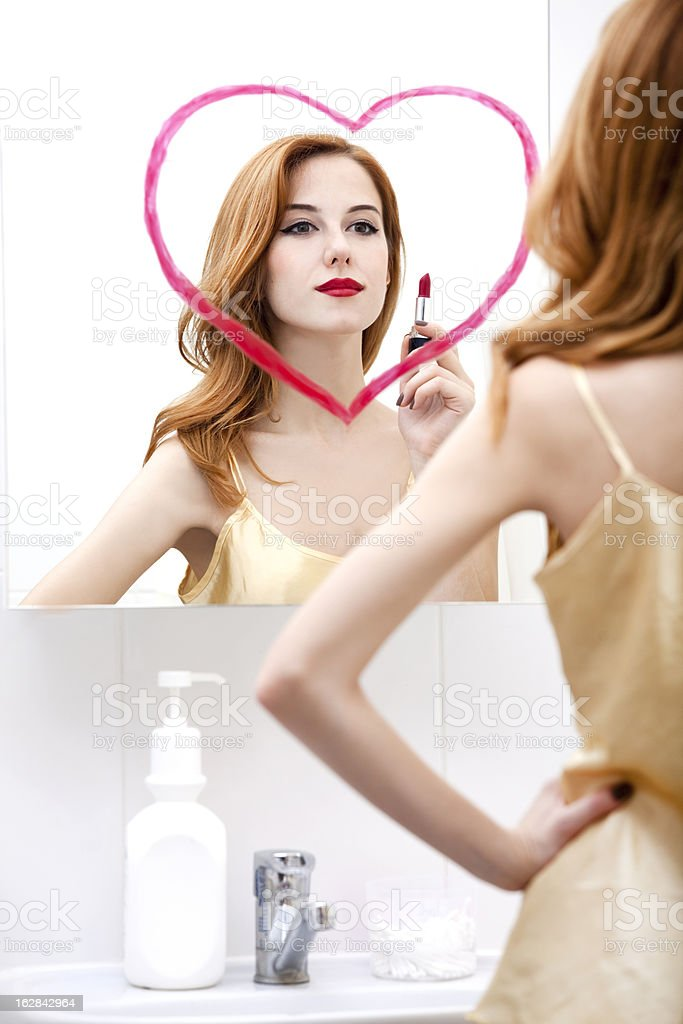 Redhead girl near mirror with heart it in bathroom. royalty-free stock photo