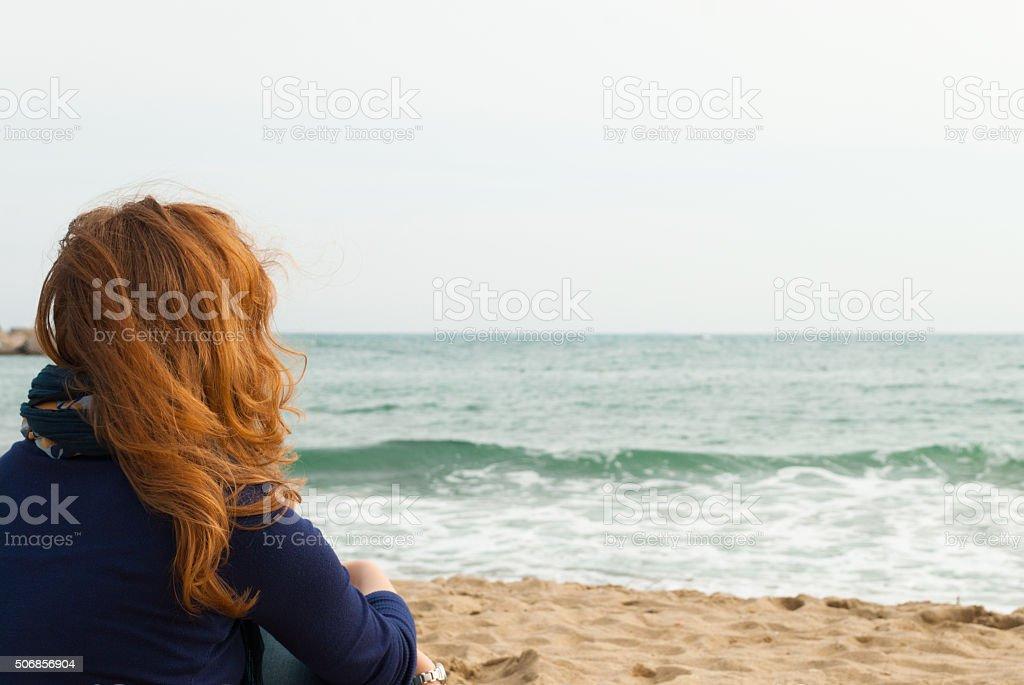 Redhead girl on a Barcelona sand beach stock photo