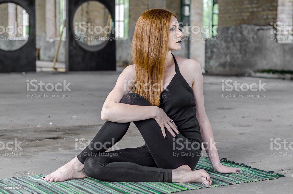 redhead girl with black make-up exercise yoga positions stock photo