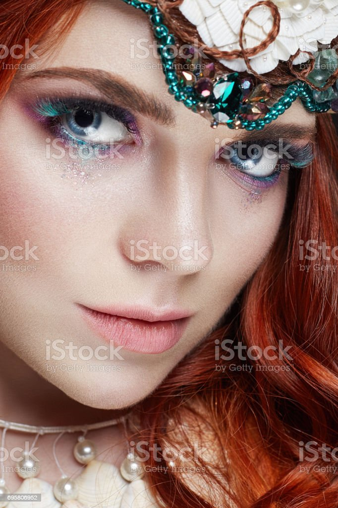 Redhead girl with bright makeup and big lashes. Mysterious fairy woman with red hair. Big eyes and colored shadows, long lashes. Sexy look, pure skin care, care face stock photo