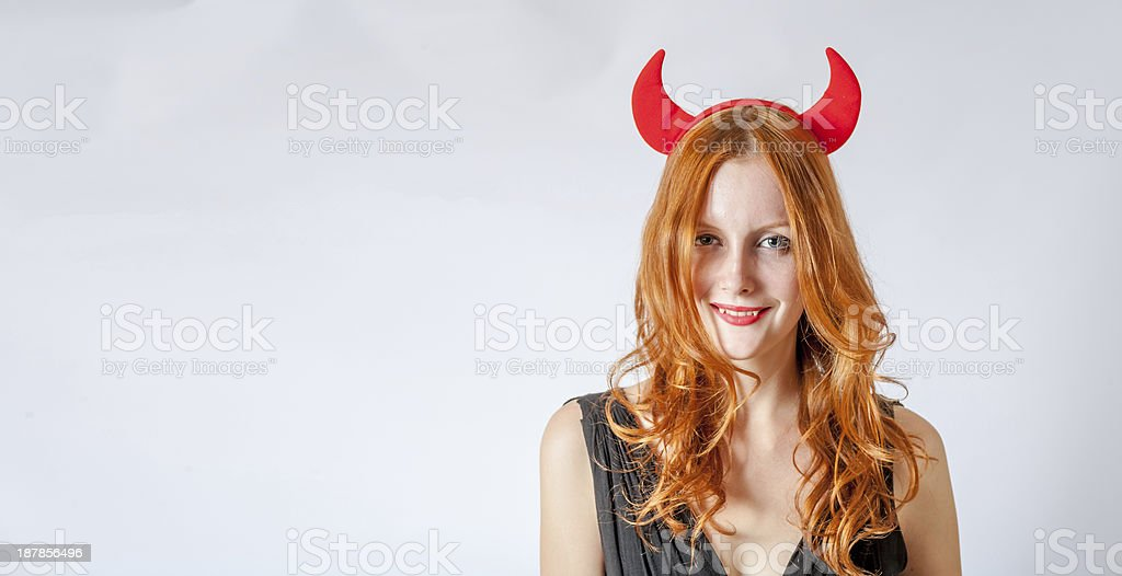 redhead girl with red  horns looks like pretty Devil stock photo
