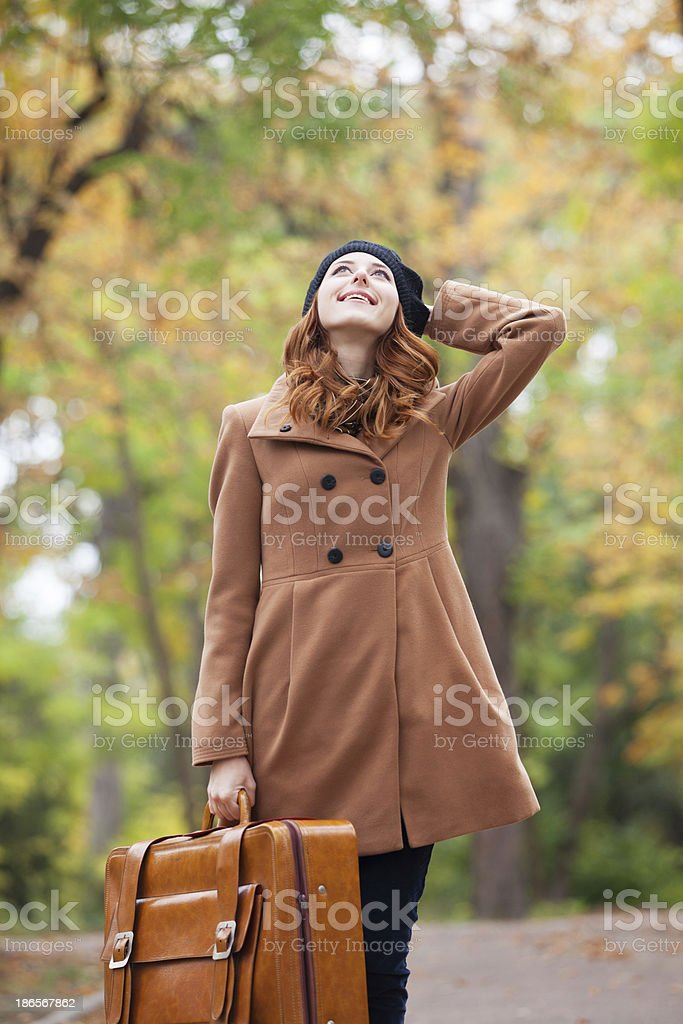 Redhead girl with suitcase at autumn outdoor royalty-free stock photo