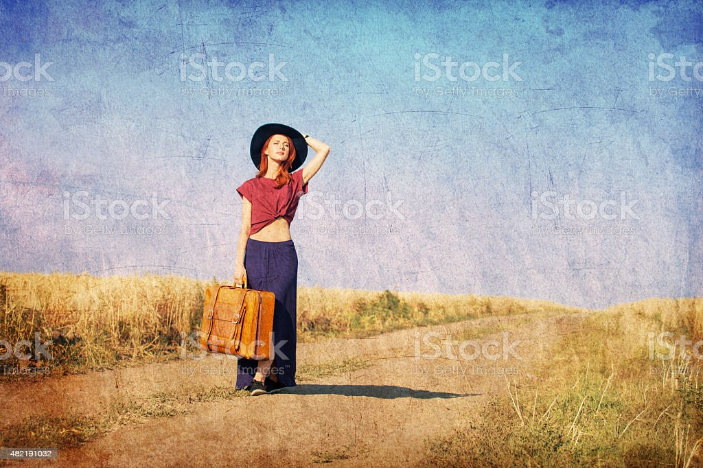 Redhead girl with suitcase at countryside road stock photo