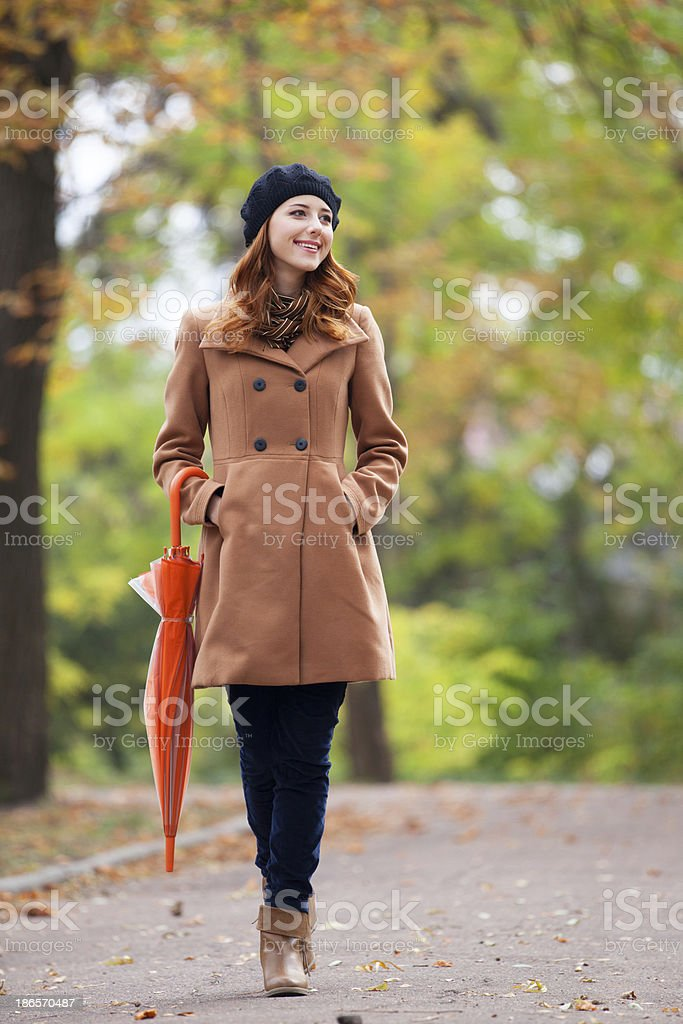 Redhead girl with umbrella at autumn outdoor royalty-free stock photo