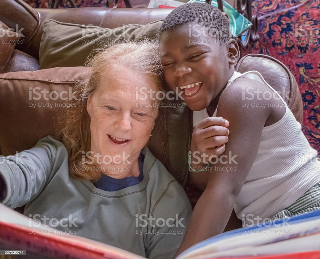 Redhead Grandmother Reading Story Book, Black Adopted Grandson, multiracial family stock photo