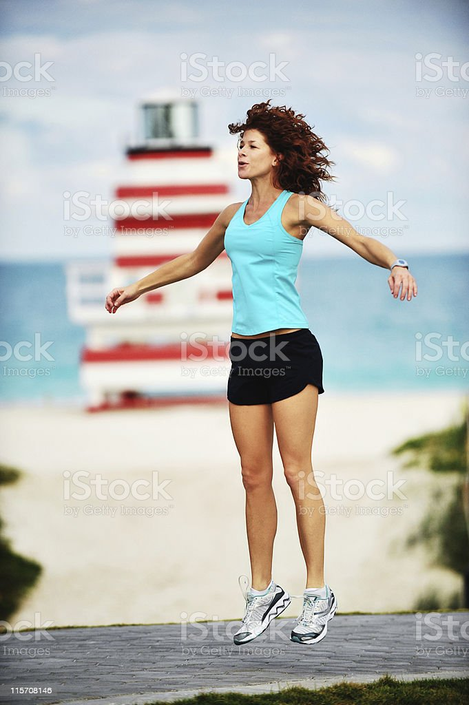 Redhead Jumping Jacks at Beach stock photo