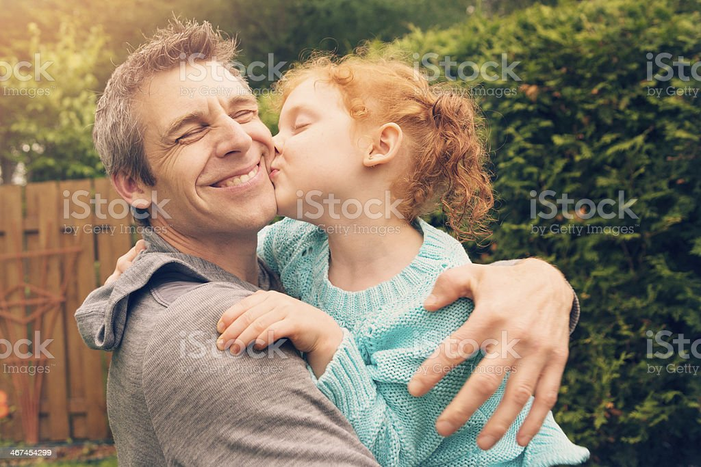 Redhead little girl kissing and hugging father outdoors. stock photo