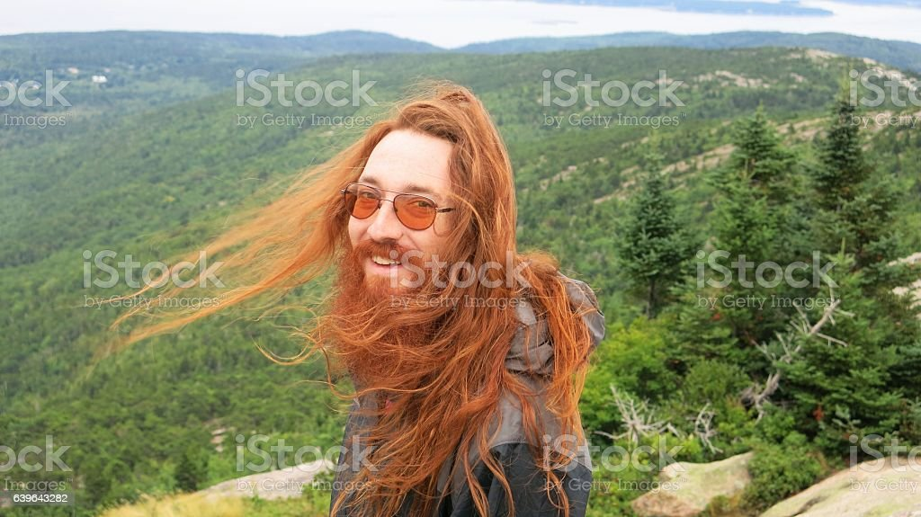 Redhead Man Long Hair Blowing in Wind, Cadillac Mountain, Maine stock photo