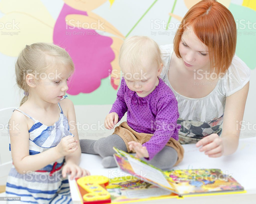 Redhead mother and blonde daughters reading a book at table royalty-free stock photo