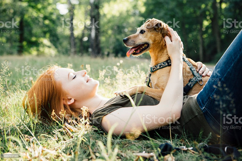 redhead teenage girl and her dog have fun outdoors stock photo