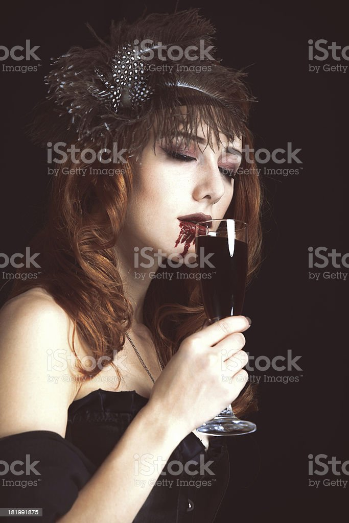 Redhead vampire woman with glass of blood. stock photo