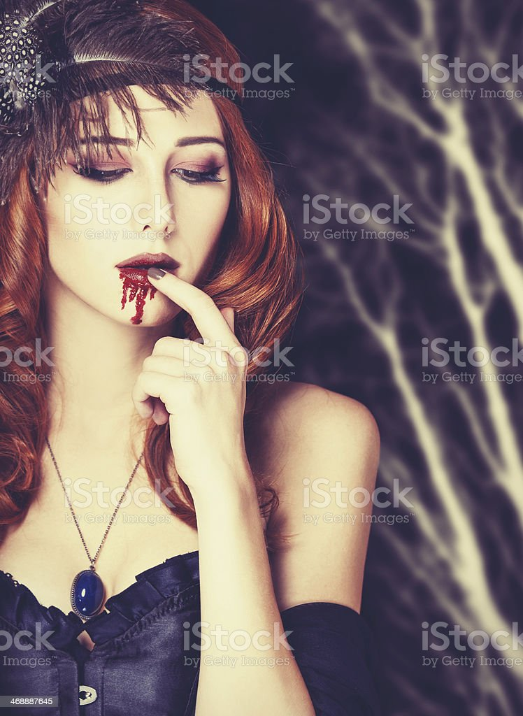 Redhead vampire woman with glass of blood. royalty-free stock photo