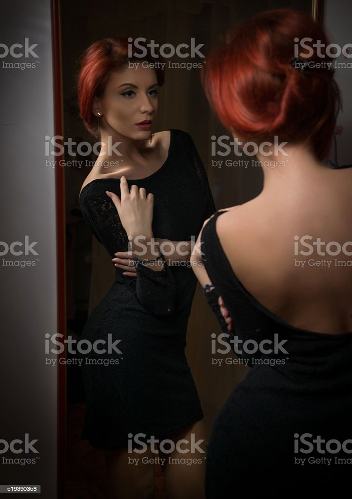 Redhead with black dress posing in front of mirror stock photo