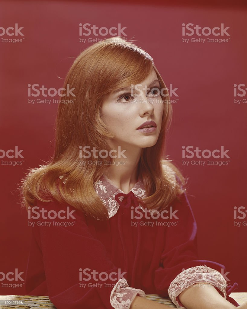 Redhead woman against red background stock photo