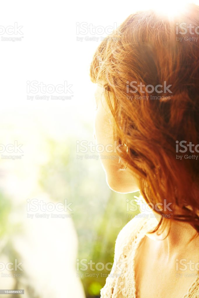 Redhead woman backlit by sun looking out to nature stock photo