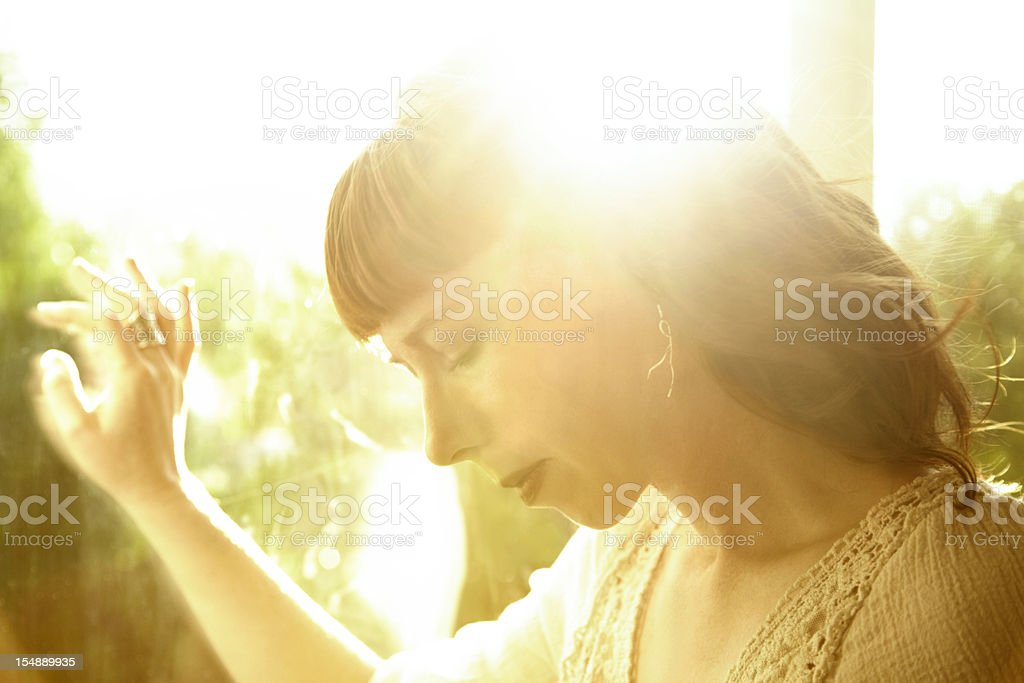 Redhead woman backlit by sun with hand on glass window royalty-free stock photo