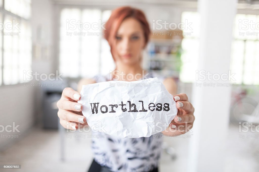 Redhead woman holding sheet of paper with message 'worthless' stock photo