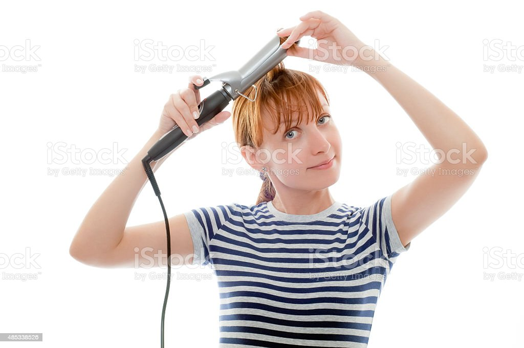 Redhead woman in striped t-shirt using curling iron stock photo