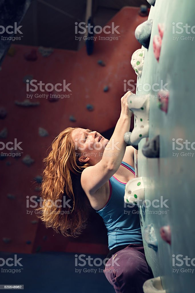 Redhead Woman Indoor Rock Climbing. Strong Heroic Female stock photo