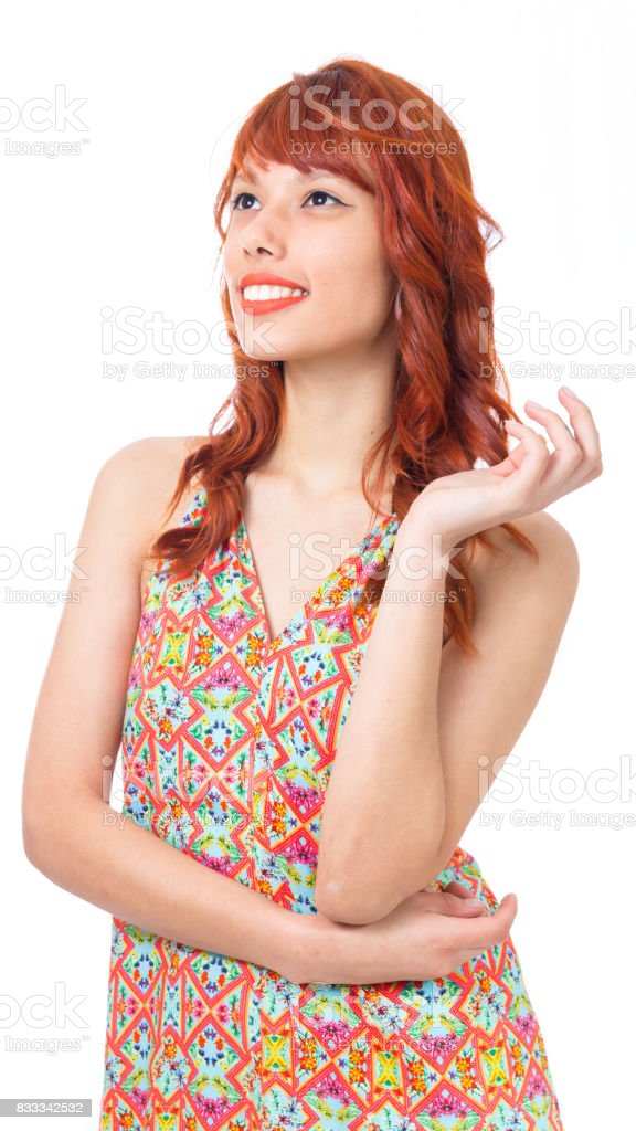 Redhead woman is wearing a colorful summer dress. Fashion and style. Vacation and summer. stock photo