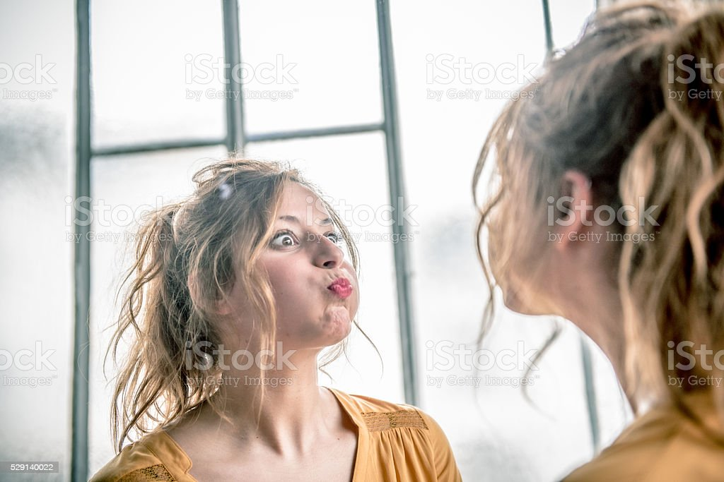 Redhead Woman Making Faces in mirror, Paris, France stock photo