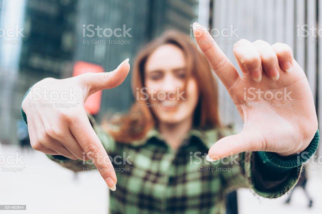 Redhead woman making finger frame stock photo