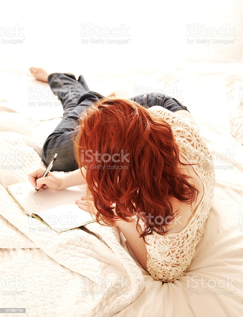 Redhead woman writing in her journal on a bed royalty-free stock photo